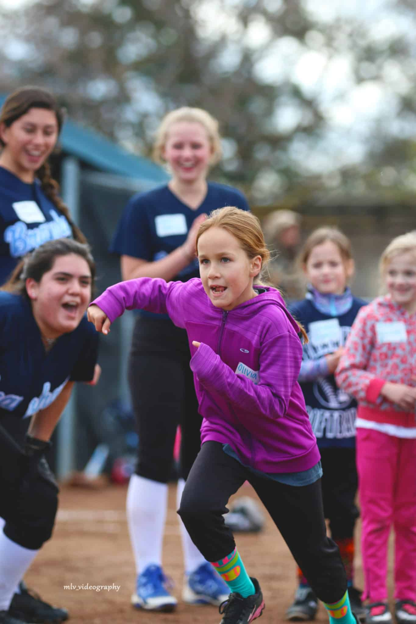 Action shot of a softball player running the bases with supportive clinic coaches in background
