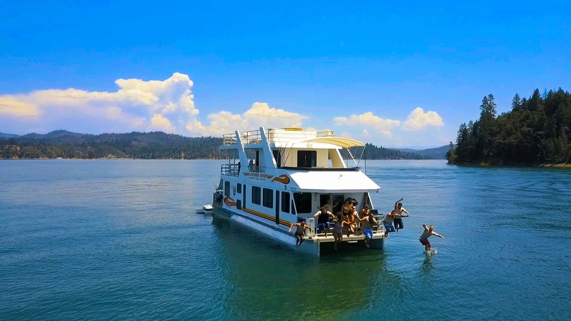 Jumping off the front of a houseboat on Lake Shasta, taken from a drone 100 ft away